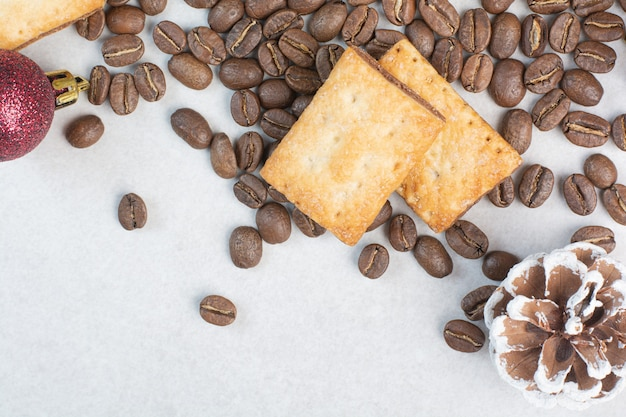 Aromakaffeebohnen mit crackern auf weißem hintergrund. hochwertiges foto