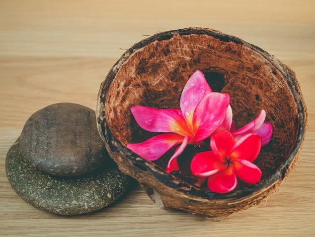 Aromaöl in der kokosnussschale mit spa steinen.