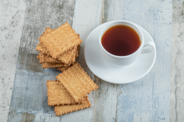 Aromatasse tee mit leckeren crackern auf einem holztisch.