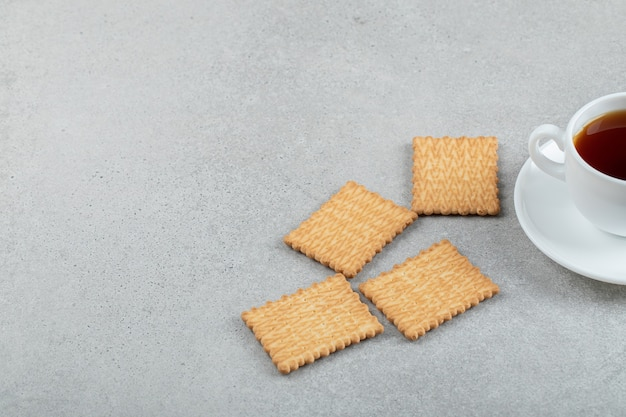 Aromatasse tee mit leckeren crackern auf einer marmoroberfläche.