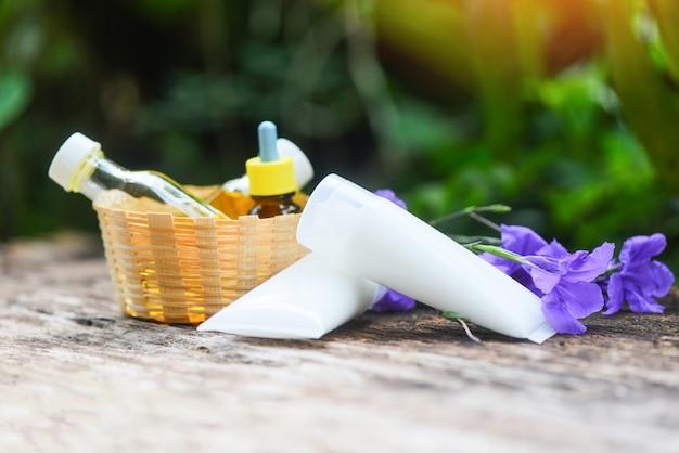 Aromatherapie-kräuteröl füllt aroma mit der blume ab, die auf holz purpurrot ist