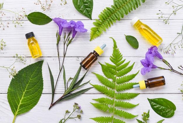 Aromatherapie-kräuterölflaschenaroma mit blume verlässt kräuterformulierungen einschließlich wildblumen und kräuter auf holz