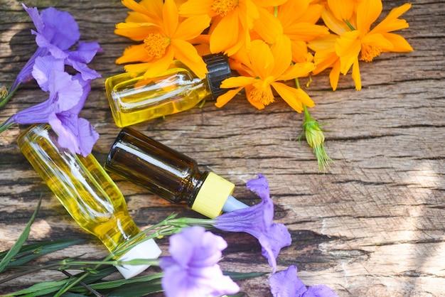 Aromatherapie-kräuterölflaschenaroma mit gelben wildblumen - ätherische öle natürlich für gesichts- und körperschönheitsmittel auf holztisch und organischem unbedeutendem lebensstil
