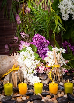 Aromatherapie, spa, schönheitsbehandlung und wellness mit massagestein, blumen, brennenden kerzen