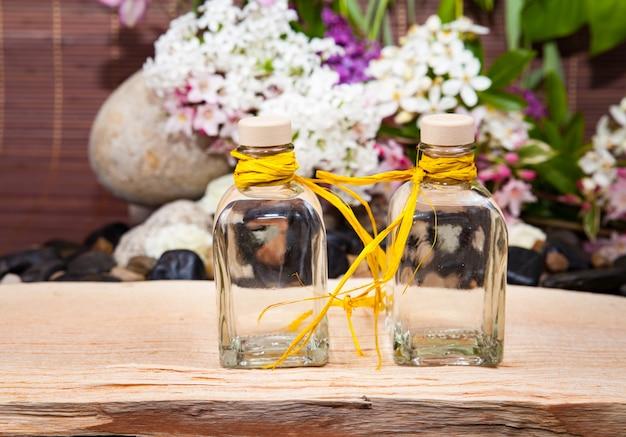 Aromatherapie, spa, schönheitsbehandlung und wellness mit massagestein, blumen, flakon