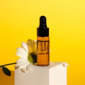 Aromatherapie-zusammensetzung auf gelber wand. kamille ätherisches öl in einer glasflasche mit kamille.