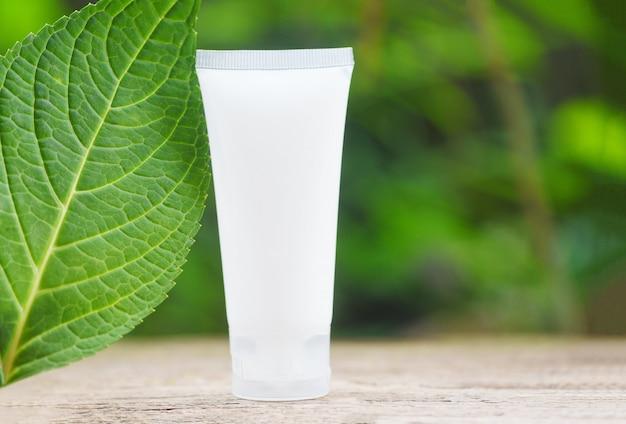 Aromatherapielotion kräuter mit grünen blättern auf holz und naturgrün, natürliche flasche der lotion für gesichts- und körperschönheitsmittel und organischer unbedeutender lebensstil des badekurortes