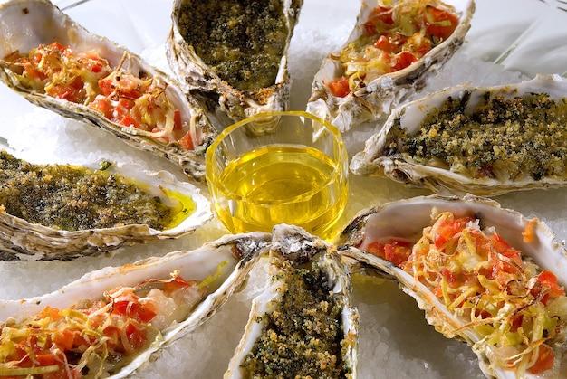 Aromatisch sortierte austern, mit lauch, tomate, parmesan und butter und mit gehackten zwiebeln.