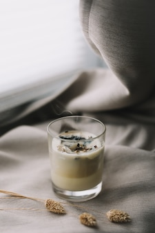 Aromatische duftkerze mit rauch und getrockneten blumen auf beigem textil