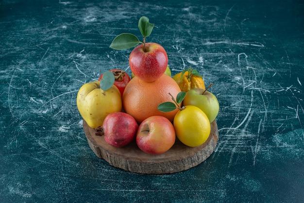 Aromatische früchte auf dem brett, auf dem blauen hintergrund. hochwertiges foto