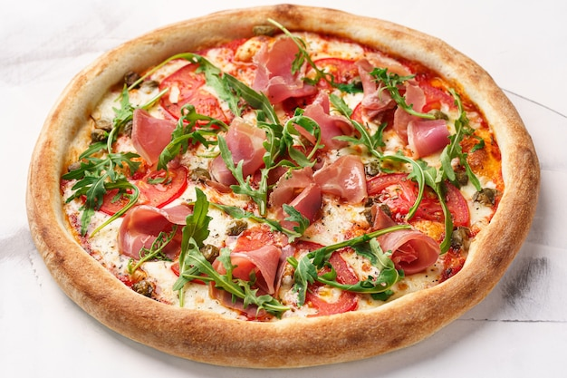 Aromatische italienische pizza mit schinken-tomaten-käse-rucola-kapern-tomaten