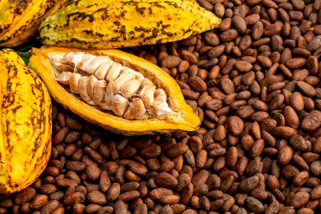 Aromatische kakaobohnen als hintergrund, kakaobohnen und kakaofrüchte auf hölzernem.