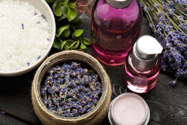 Aromatische komposition aus lavendel, kräutern, kosmetik und salz auf dunkler tischplatte