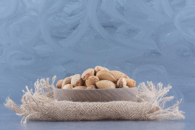 Aromatische mandeln ergießen sich aus einer schüssel auf dem marmorhintergrund.
