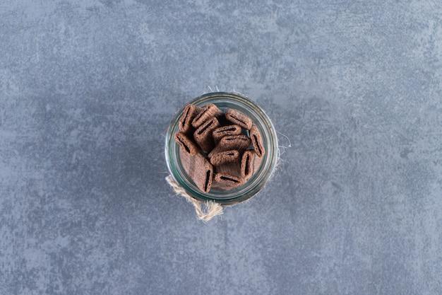 Aromatische schokoladenwaffelrolle im glas auf der marmoroberfläche