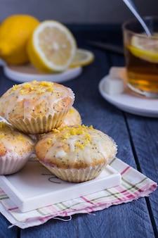 Aromatische selbst gemachte zitronen-und mohn-muffins mit tasse tee auf dem grauen hintergrund