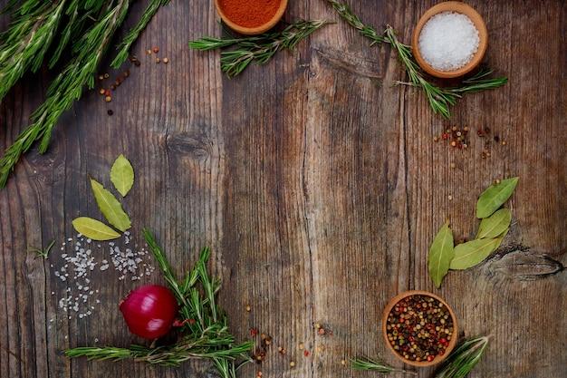 Aromatische trockene kräuter und gewürze auf holztisch. draufsicht.