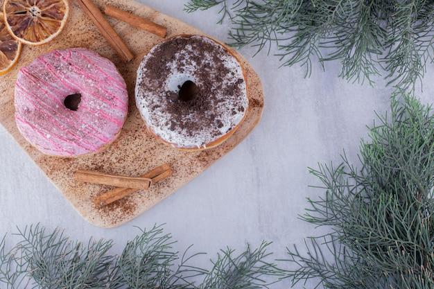 Aromatische zimtstangen, donuts und getrocknete orangenscheiben auf einem brett auf weißem hintergrund.