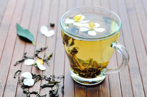 Aromatischer grüner tee mit jasminblüten im glas auf hölzernem hintergrund
