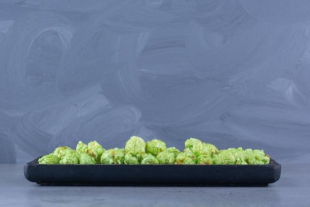 Aromatischer haufen popcorn-bonbons auf einem kleinen tablett auf marmoroberfläche