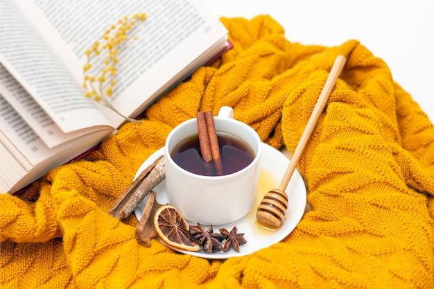 Aromatischer heißer zimttee bedeckt mit einem warmen schal auf einem hölzernen herbsthintergrund. honigschöpflöffel mit honig. bequem ein buch lesen
