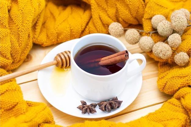Aromatischer heißer zimttee bedeckt mit einem warmen schal auf einem hölzernen herbsthintergrund. honigschöpflöffel mit honig