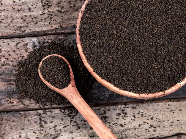 Aromatischer schwarzer tee lose oder getrocknete teeblätter auf holztisch