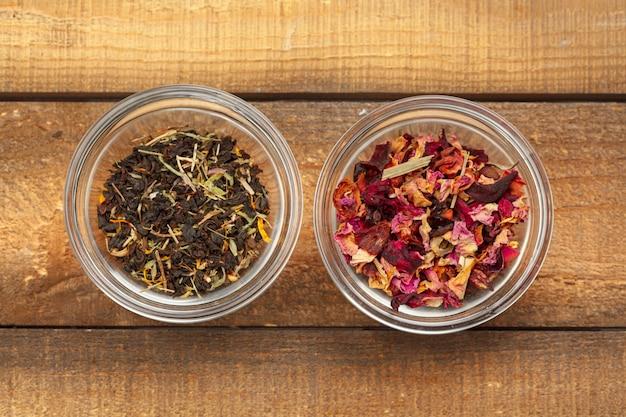 Aromatischer trockener tee in den schüsseln auf hölzernem hintergrund