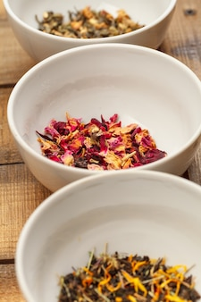 Aromatischer trockener tee in den schüsseln auf hölzernem