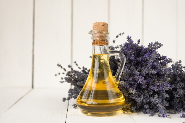 Aromatisches lavendelöl für spa-verfahren zur wiederherstellung der körperhaut. eine flasche öl auf einem lavendelstrauß.