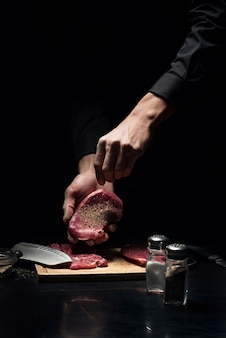 Aromatisiert und lecker. schließen sie oben von den händen der jungen männlichen köche, die das fleisch würzen, während sie im restaurant arbeiten und kochen.