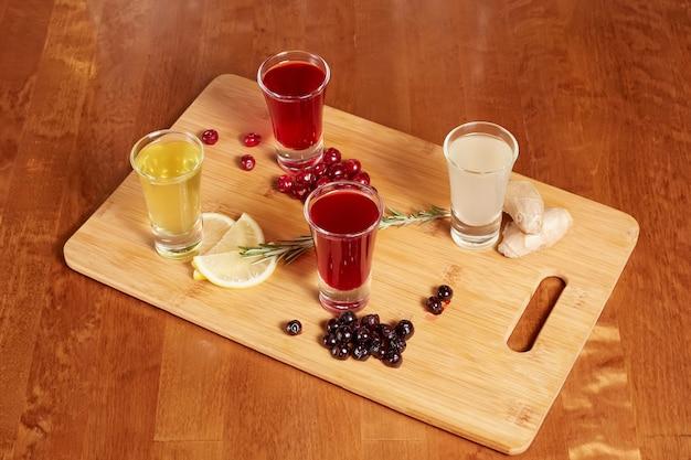 Aromatisierte fruchtliköre auf holzbrett