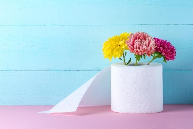 Aromatisierte toilettenpapierrolle und blumen auf einer rosa tabelle. toilettenpapier mit einem geruch. hygienekonzept. toilettenpapier-konzept.