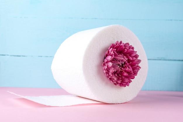 Aromatisierte toilettenpapierrolle und eine rosa blume auf einer rosa tabelle. toilettenpapier mit einem geruch. hygienekonzept