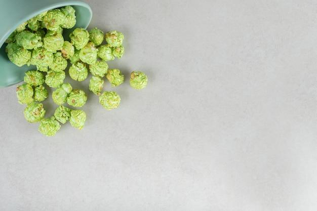 Aromatisiertes popcorn, das aus einer kleinen schüssel auf marmor auf marmor fließt.