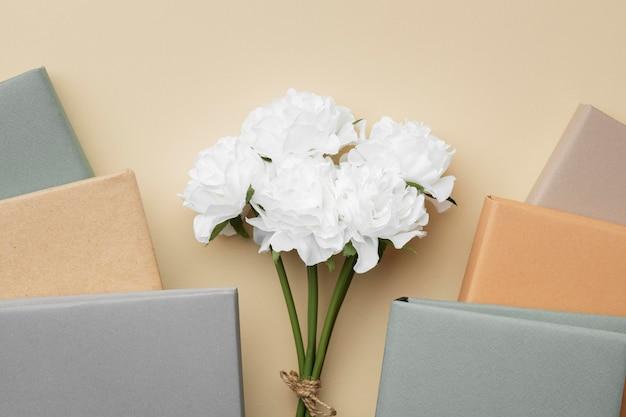 Arrangement mit büchern und weißen blumen