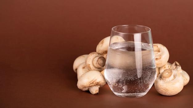 Arrangement mit champignons und einem glas wasser