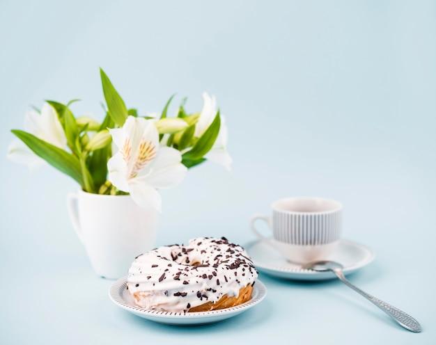 Arrangement mit donut und blumen