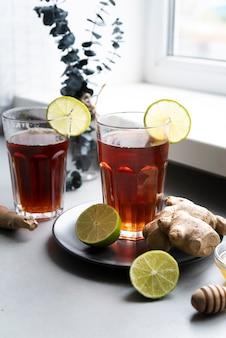 Arrangement mit einem glas tee und limette