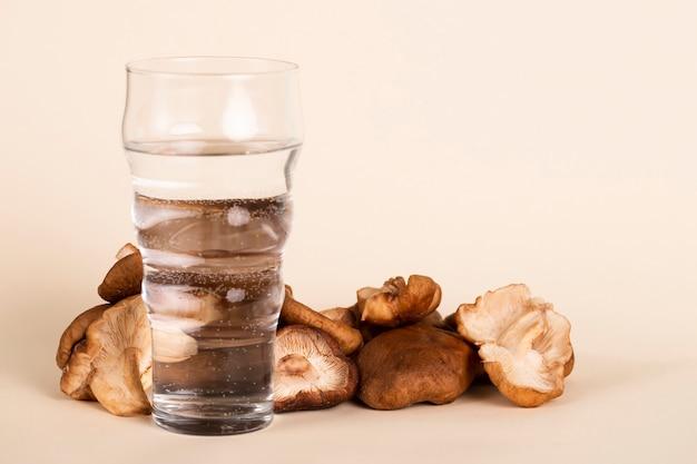 Arrangement mit einem glas wasser und champignons