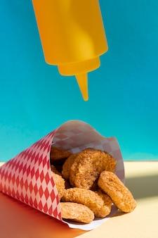 Arrangement mit einer flasche senf und nuggets