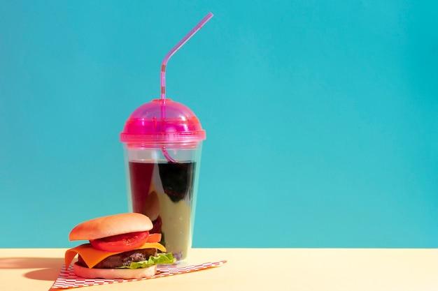 Arrangement mit einer tasse saft und cheeseburger