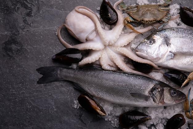 Arrangement mit frischem fisch und meeresfrüchten auf marmortisch