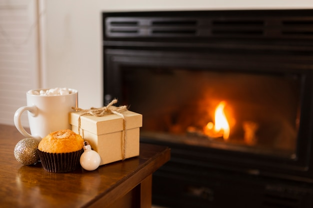 Arrangement mit geschenkbox in der nähe des kamins