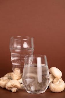 Arrangement mit gläsern und frischen pilzen