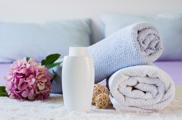 Arrangement mit handtüchern, flasche und blume auf dem bett