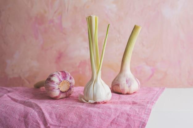 Arrangement mit knoblauch auf rosa stoff