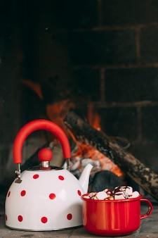 Arrangement mit teekanne und becher in der nähe des kamins
