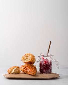 Arrangement von croissant und hausgemachter marmelade aus wilden beeren