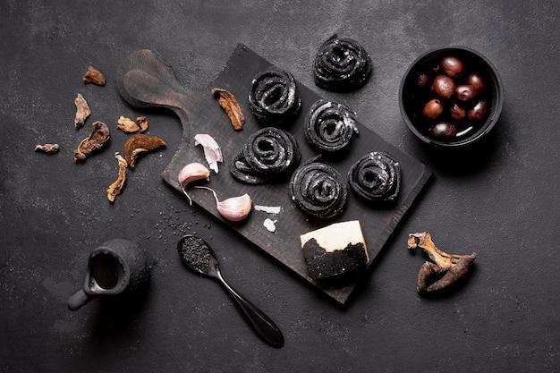 Arrangement von nudeln und oliven auf schneidebrett